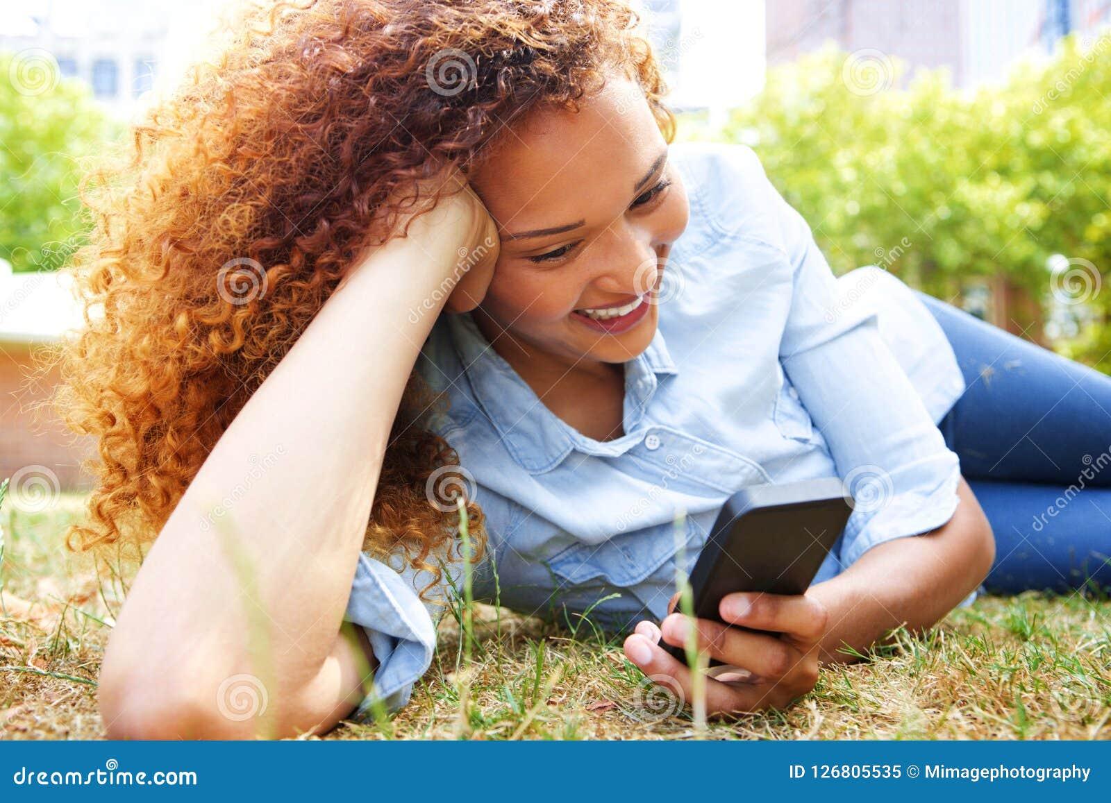 Счастливая молодая женщина лежа в траве на парке и смотря мобильный телефон