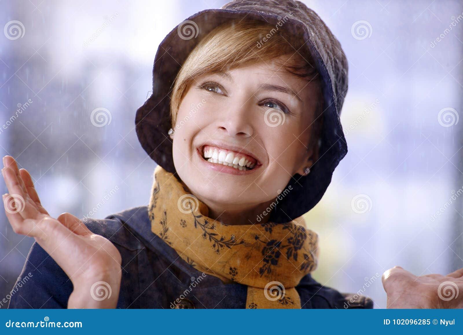 Счастливая молодая женщина наслаждаясь дождем