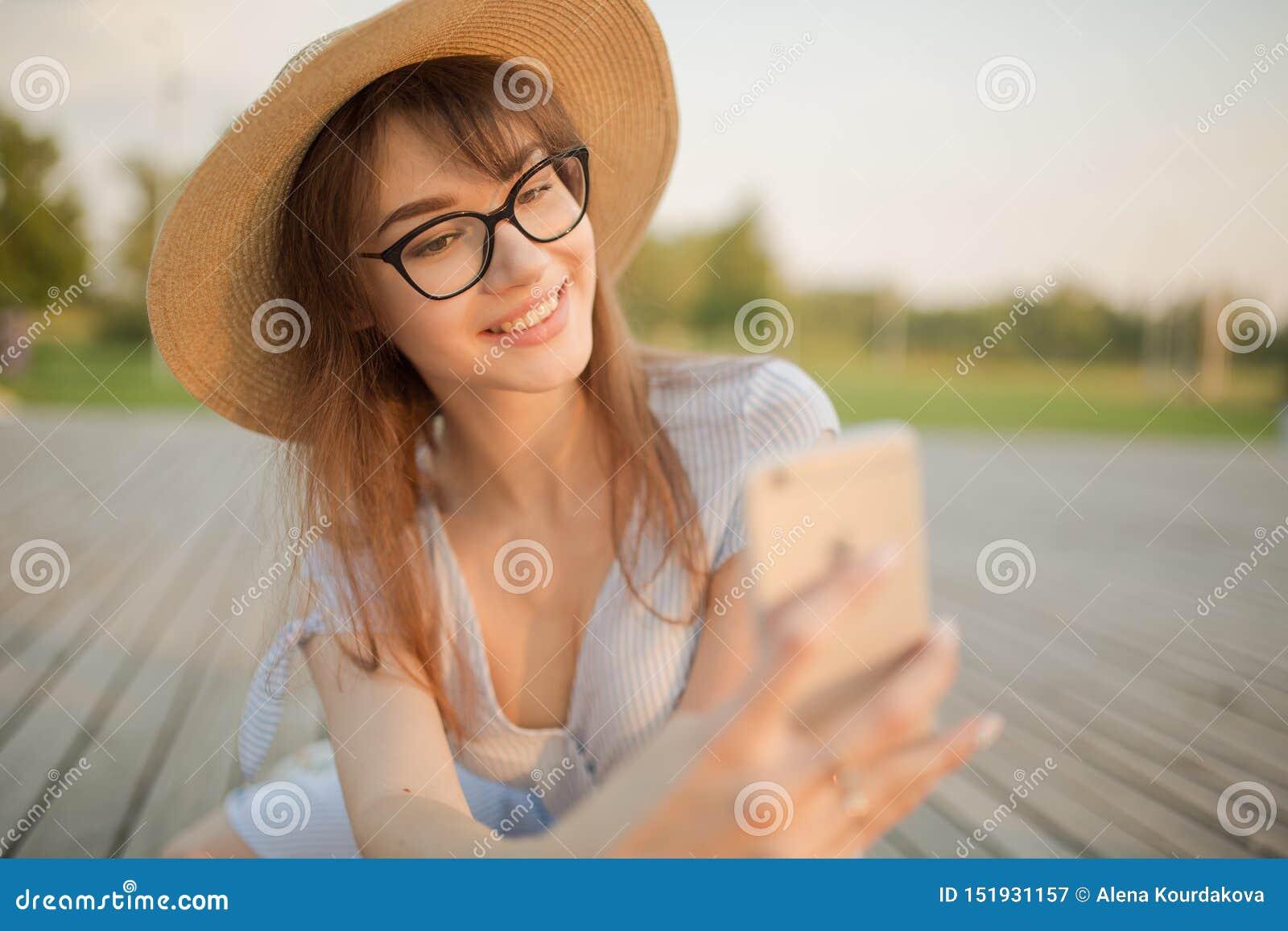 Счастливая молодая женщина сидя в парке Усмехаться делает selfie