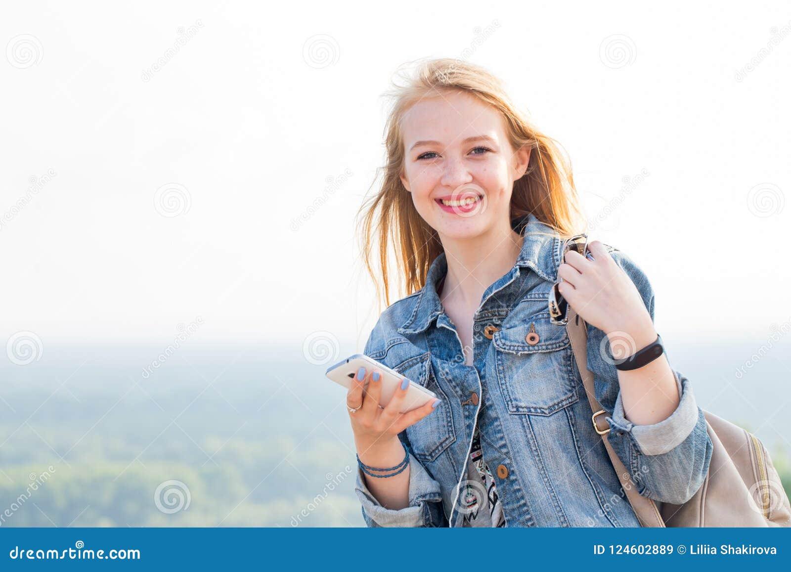 Счастливая молодая женщина с smartphone в наличии при улыбка смотря камеру Перемещение, интернет, современные технологии, телефон
