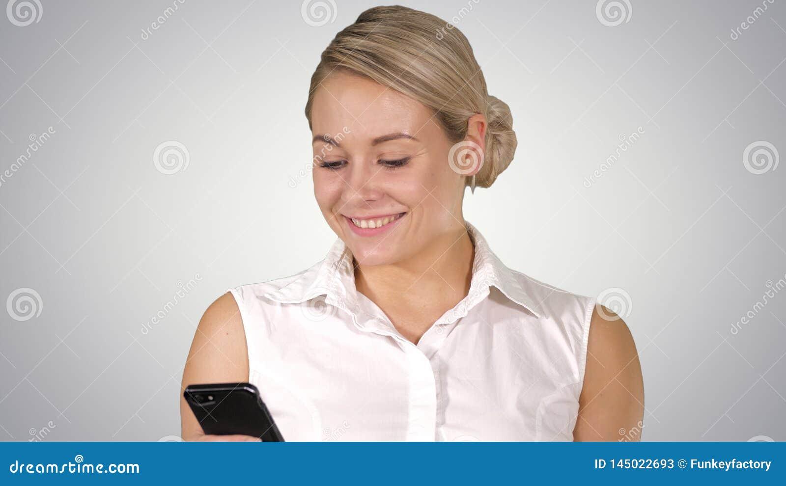 Счастливая молодая красивая женщина усмехаясь и используя мобильный телефон на предпосылке градиента