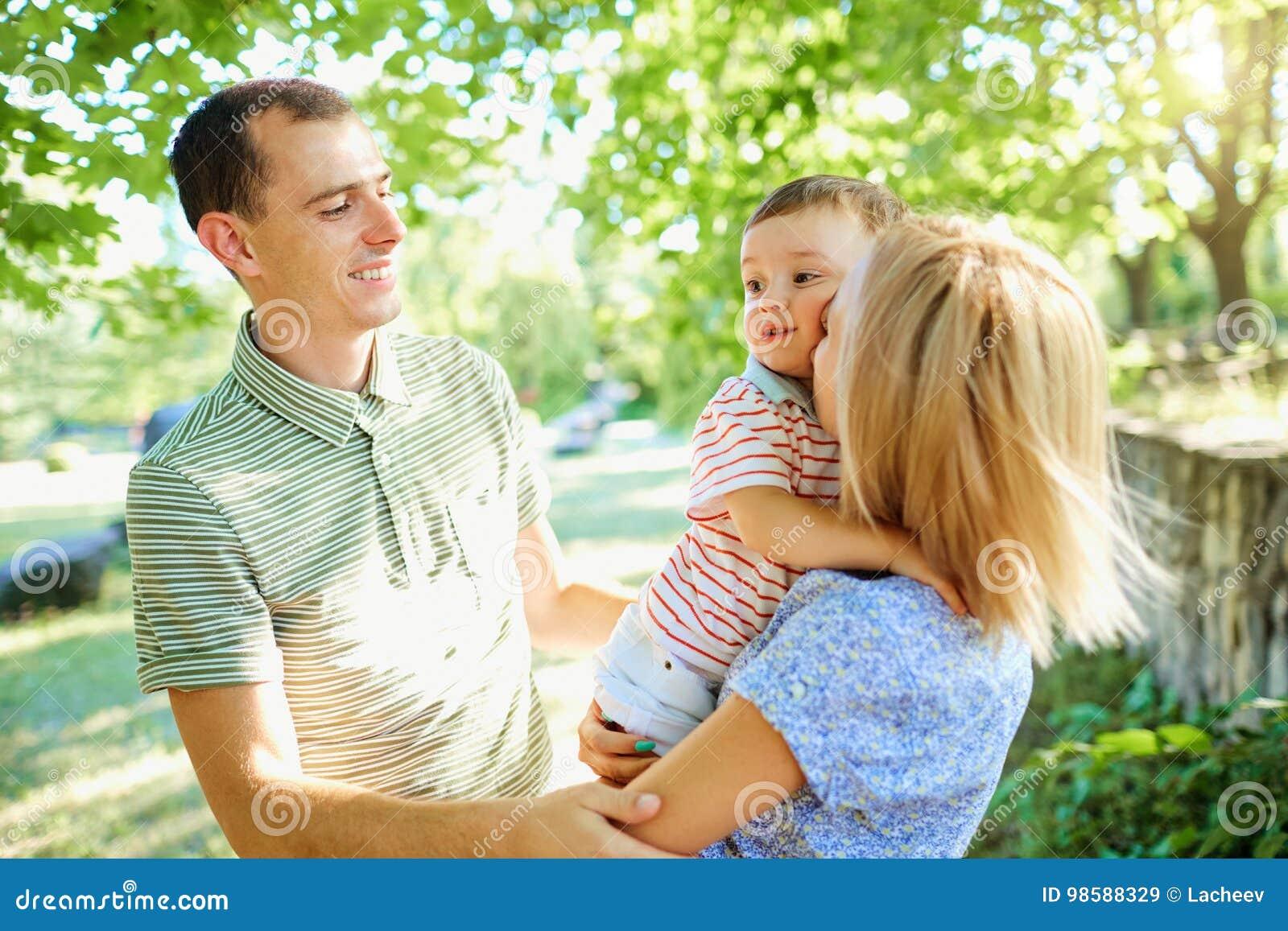 Счастливая молодая семья идя в парк лета Отец матери и освещенный