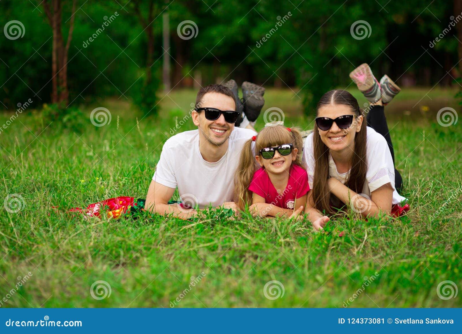 Счастливая молодая семья тратя время внешнее на летний день Счастье и сработанность в семейной жизни