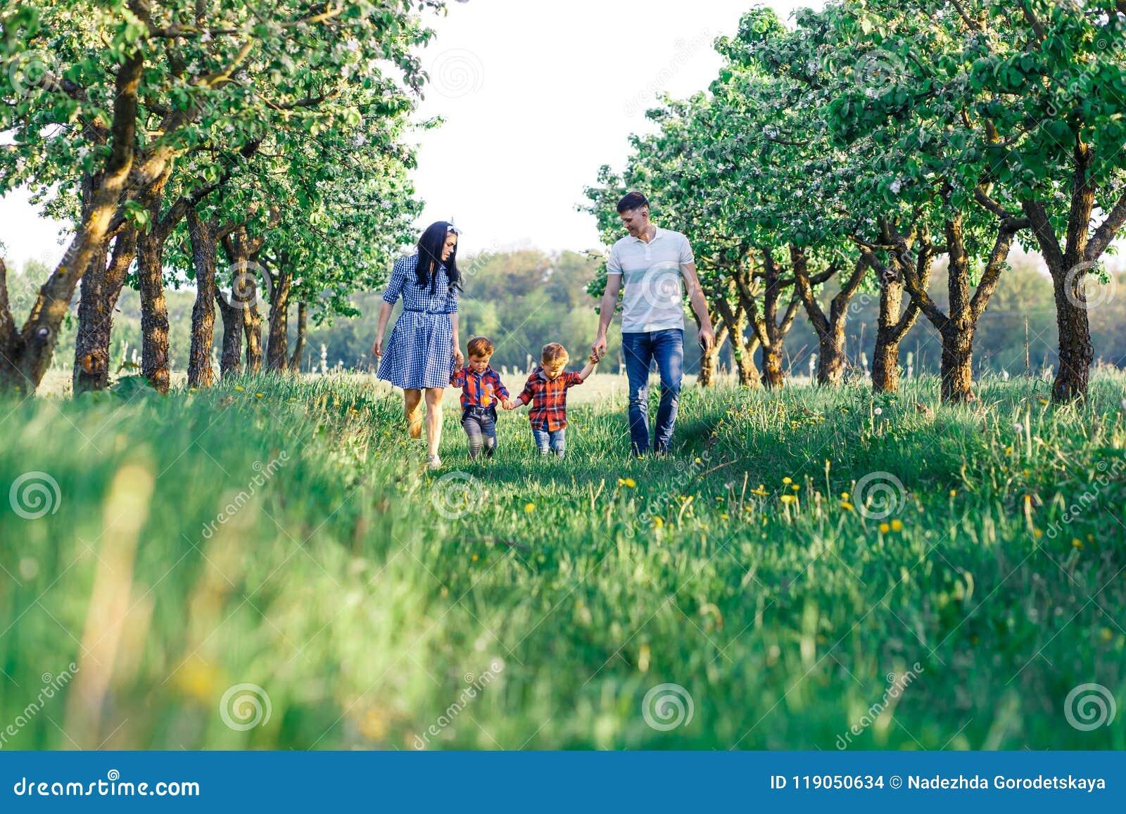Счастливая молодая семья тратя время совместно снаружи в зеленой природе Родители играя с близнецами Walkng семьи из четырех чело
