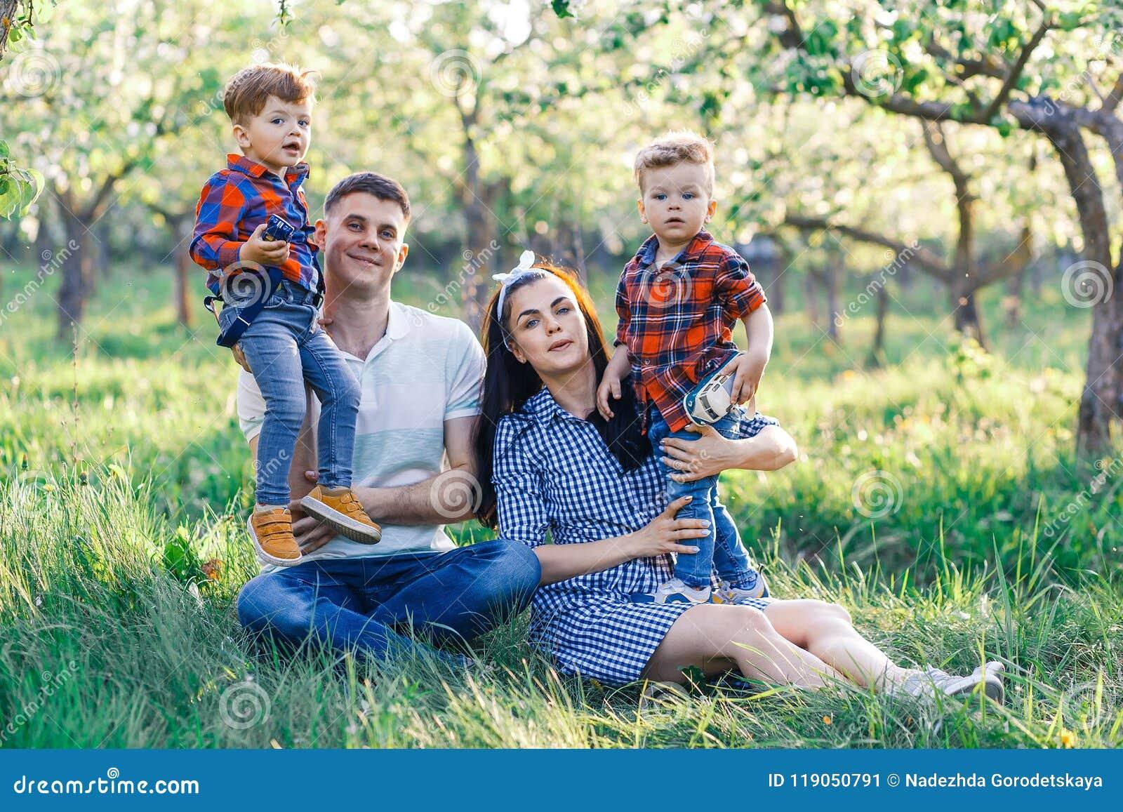 Счастливая молодая семья тратя время совместно снаружи в зеленой природе Родители играя с близнецами снаружи