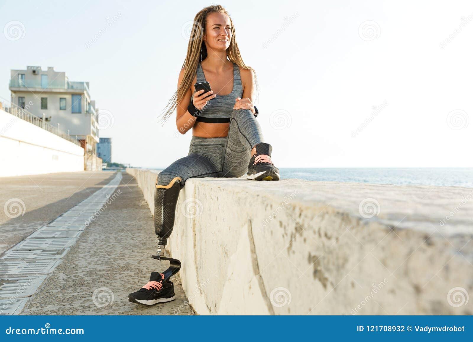 Счастливая неработающая женщина спортсмена с простетической ногой