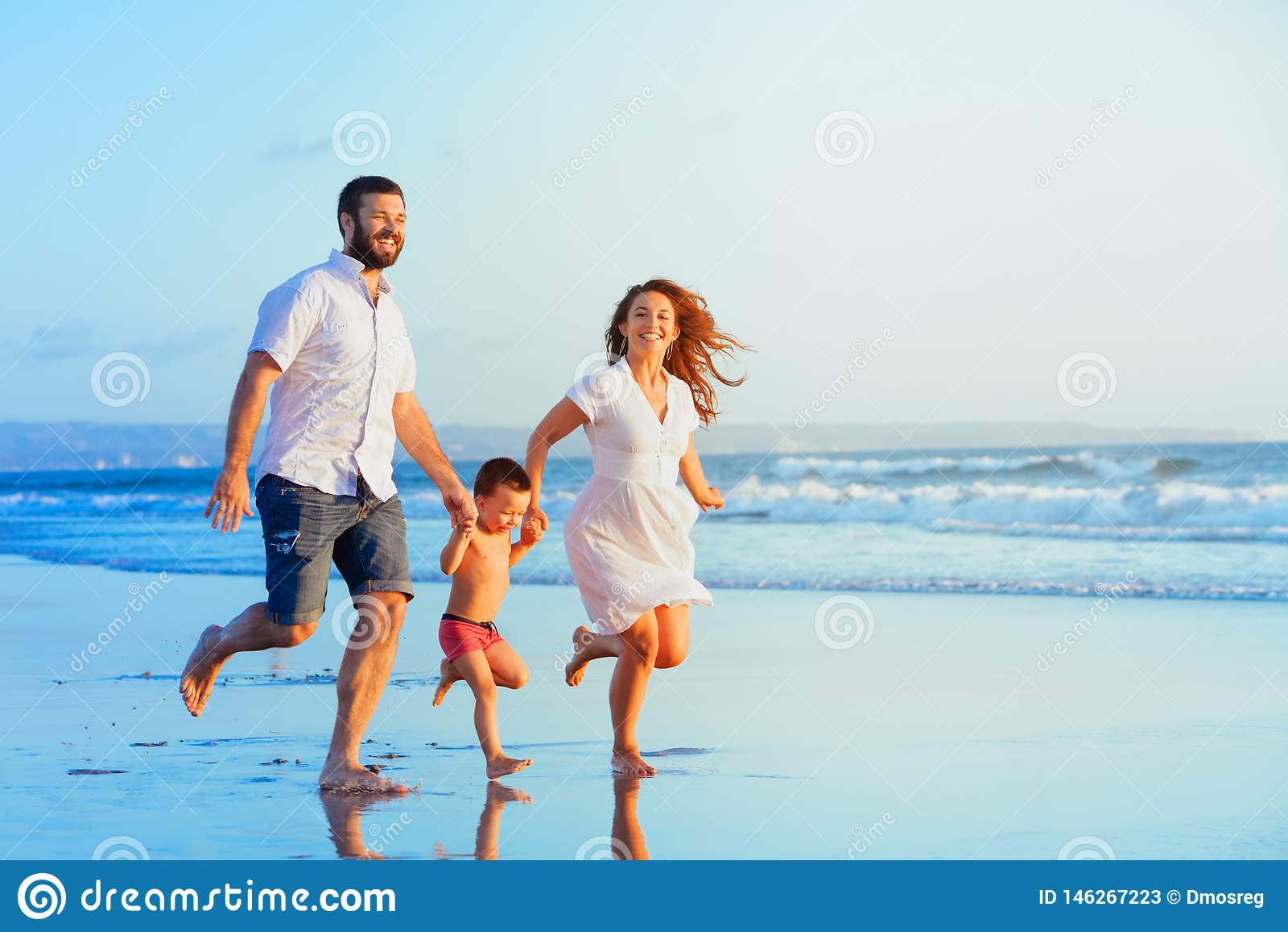 Счастливая семья бежать пляжем захода солнца