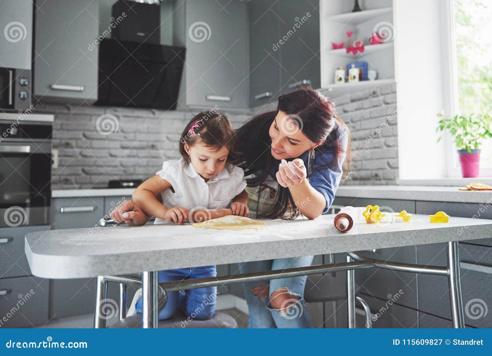 Счастливая семья в кухне Концепция еды праздника Мать и дочь подготавливая тесто, пекут печенья семья счастливая