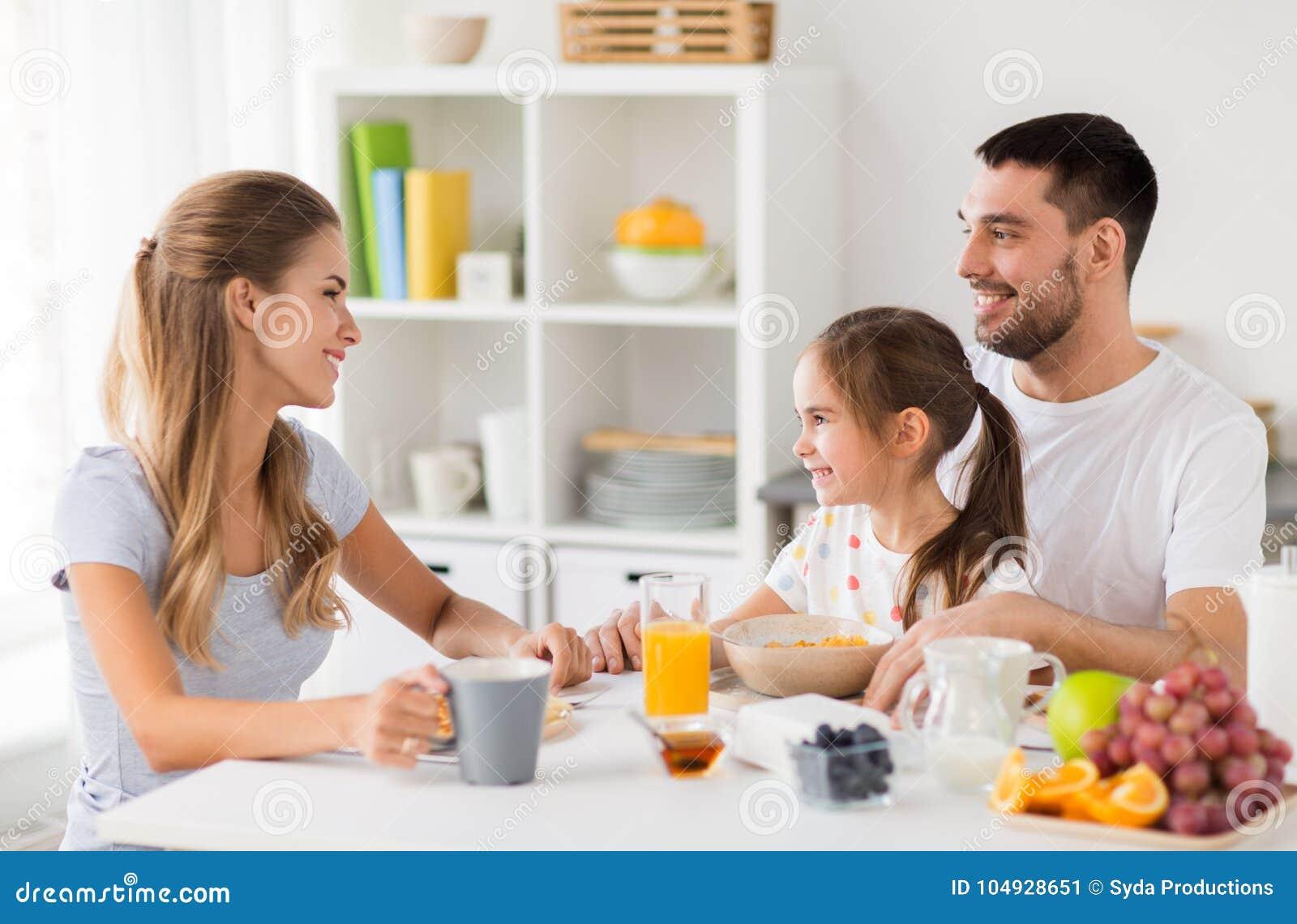 Счастливая семья имея завтрак дома