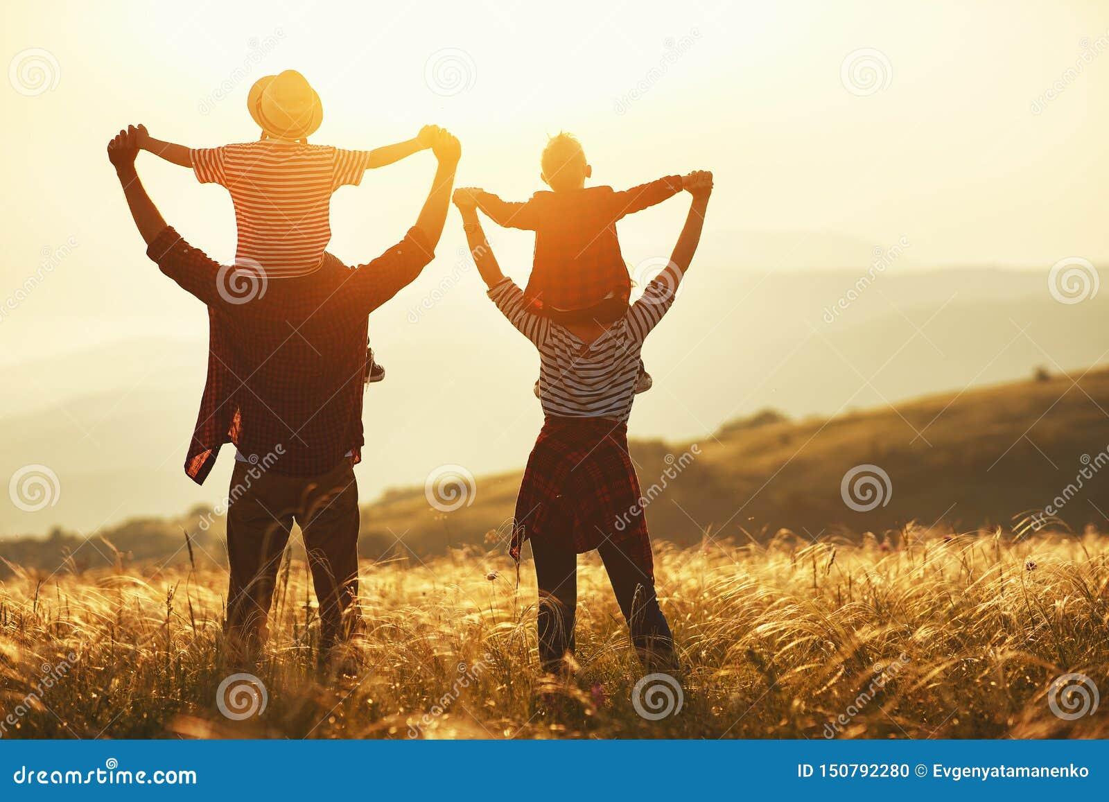 Счастливая семья: мать, отец, дети сын и дочь на заходе солнца