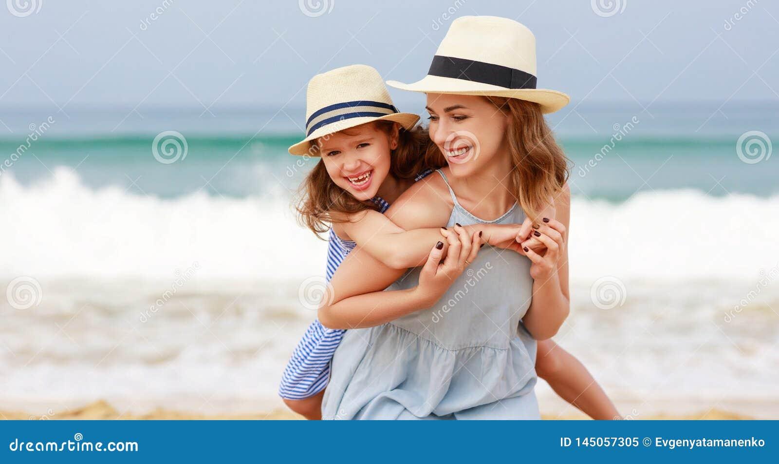 Счастливая семья на пляже объятие дочери матери и ребенка на море