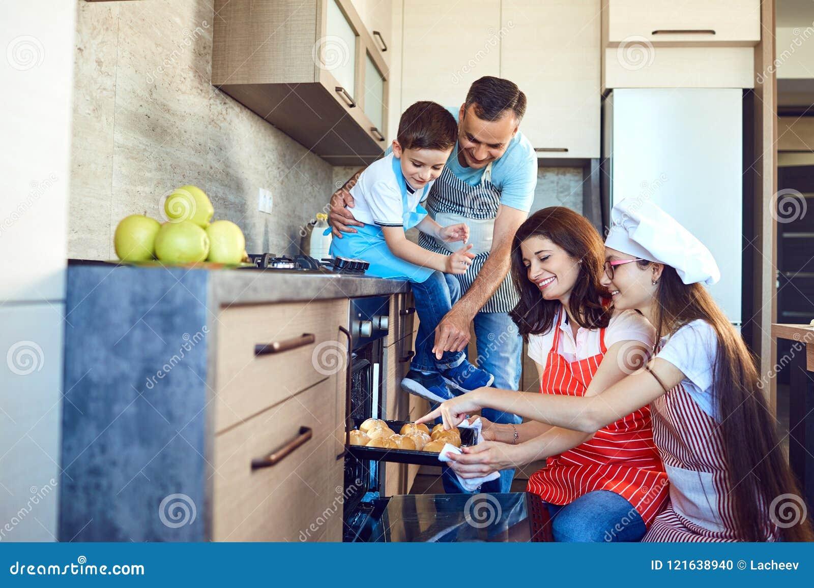 Счастливая семья печет плюшки в печи в кухне