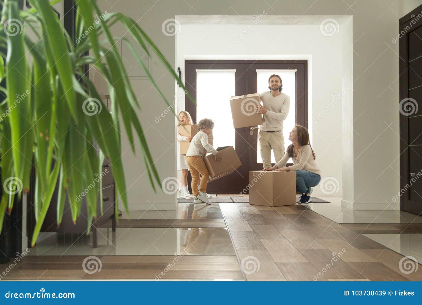 Счастливая семья при дети держа коробки двигая в новый дом