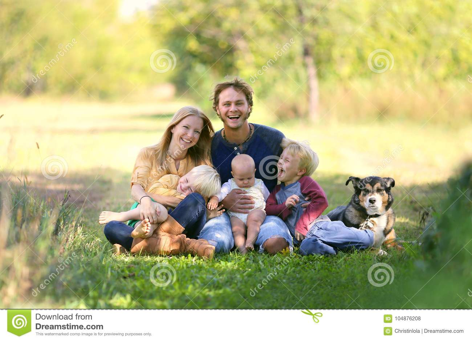 Счастливая семья смеясь над вместе с собакой снаружи