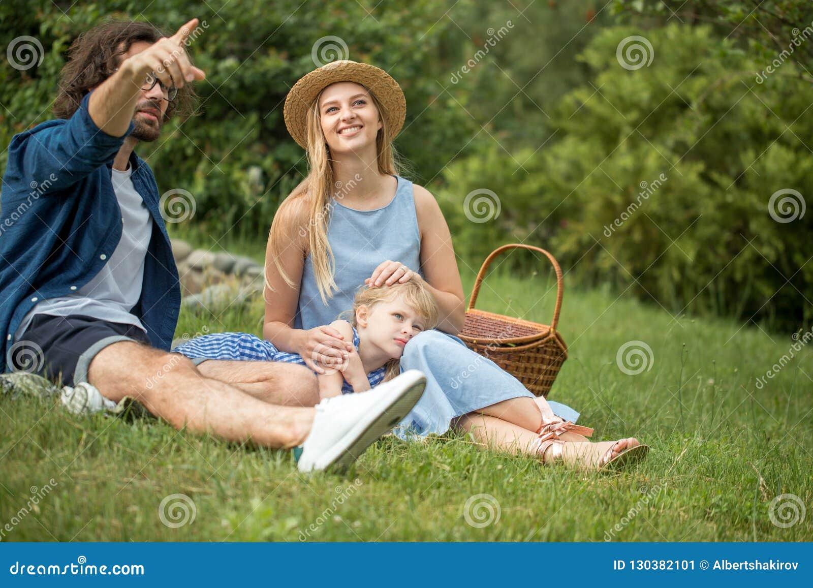 Счастливая семья участвовать outdoors с их милой дочерью, голубыми одеждами, женщиной в шляпе