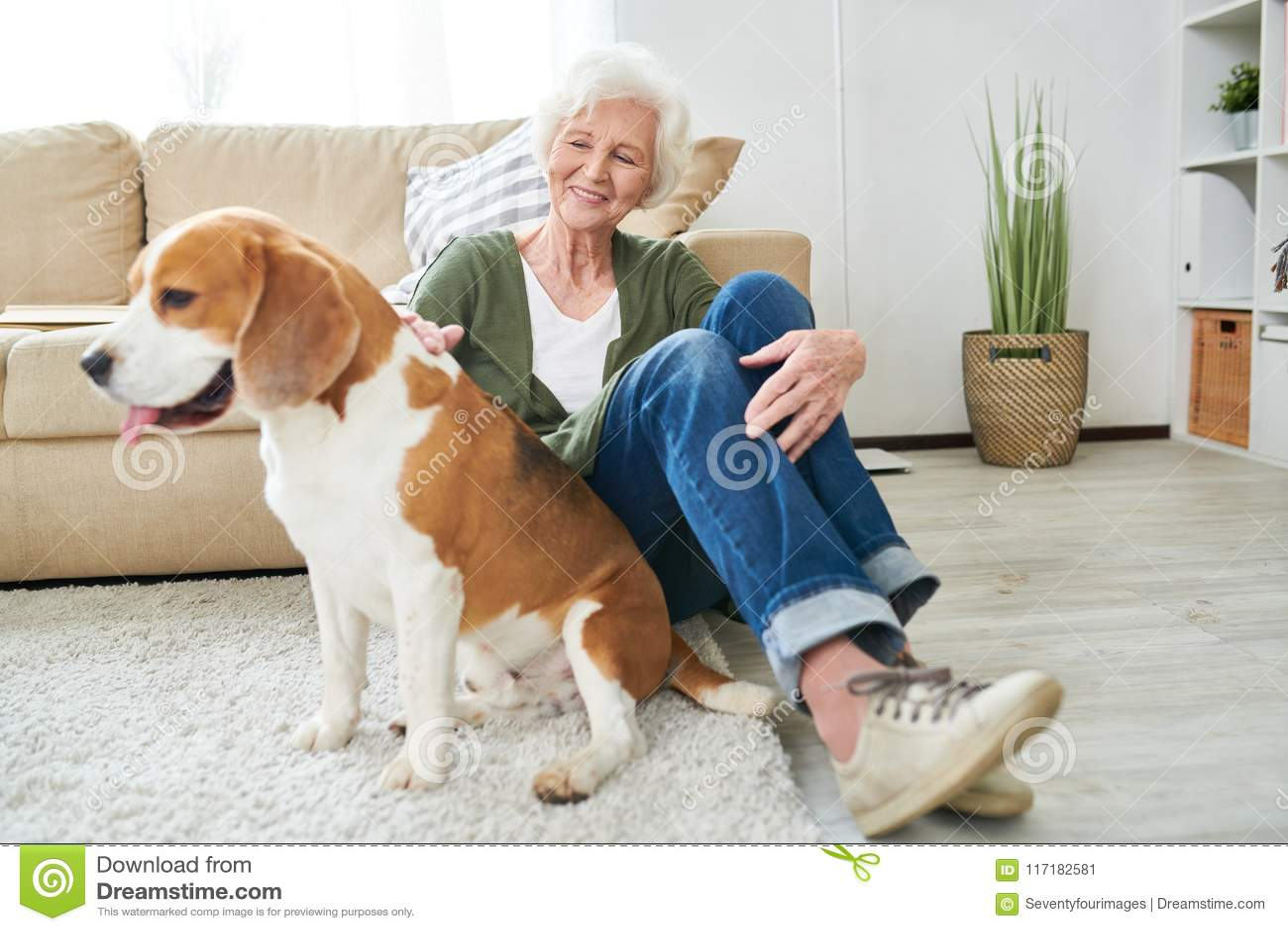 Счастливая старшая женщина играя с собакой дома