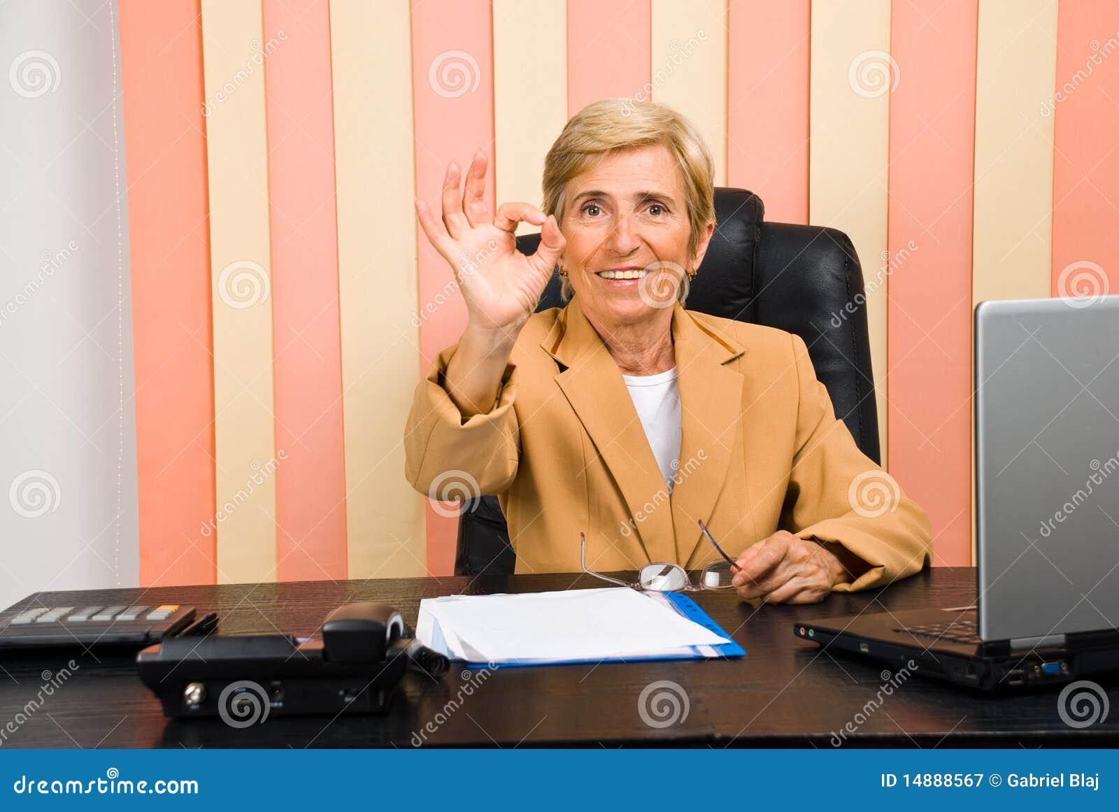 Счастливая старшая коммерсантка показывая одобренную руку знака