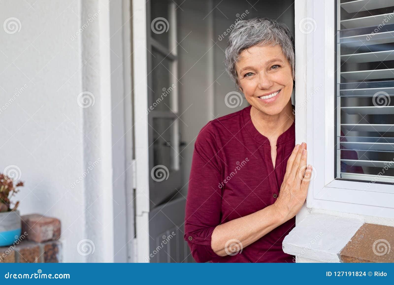 Счастливая старшая склонность женщины на двери