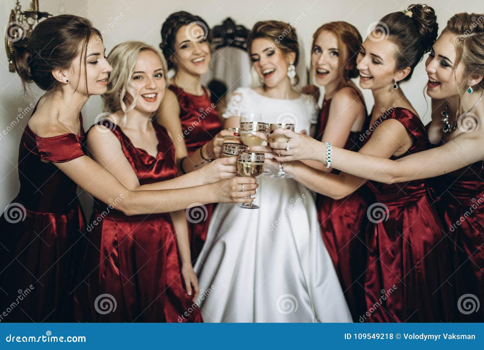 Счастливая стильная шикарная белокурая невеста с bridesmaids на задней части
