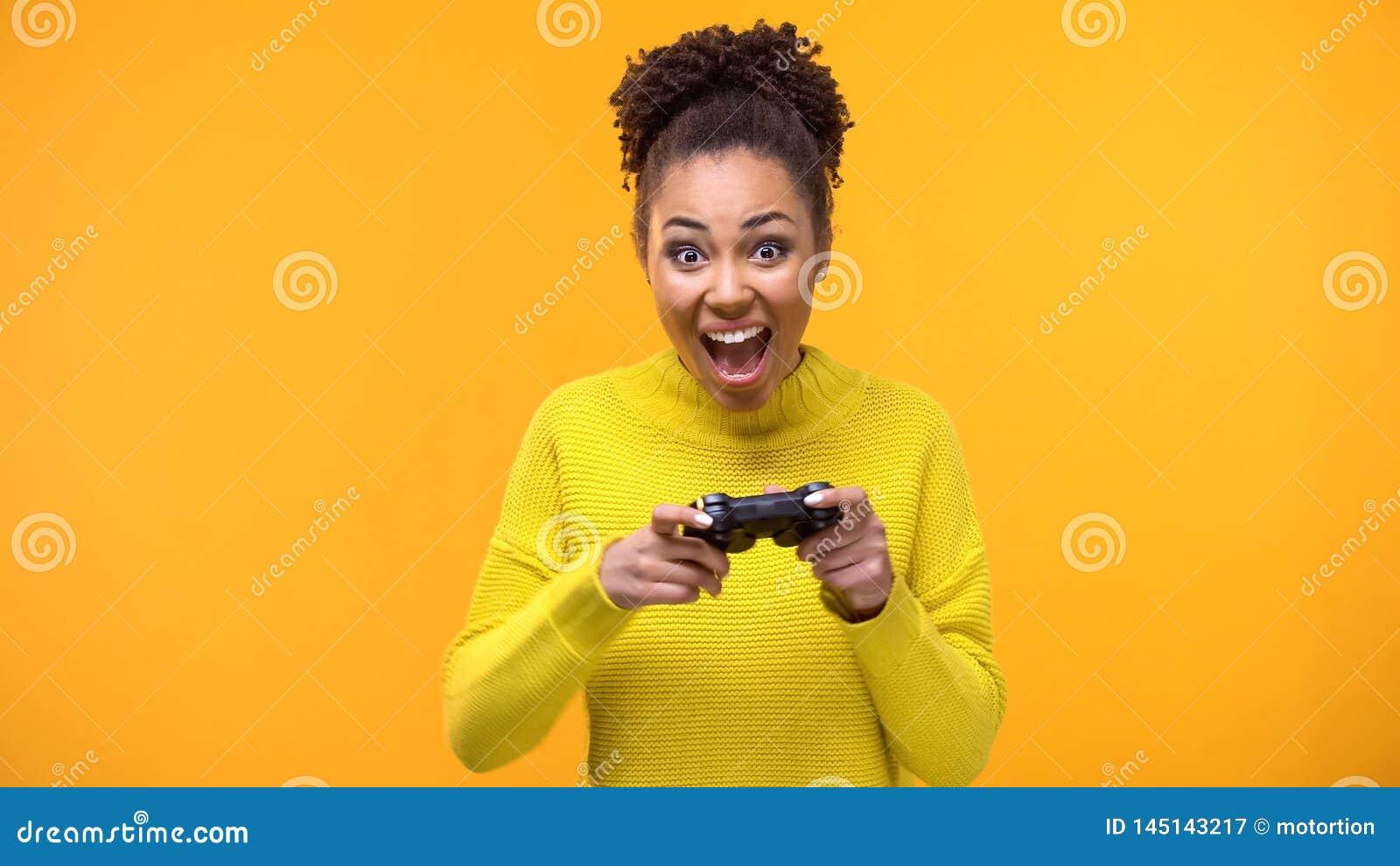 Счастливая студентка с предпосылкой кнюппеля игры желтой, ободрением