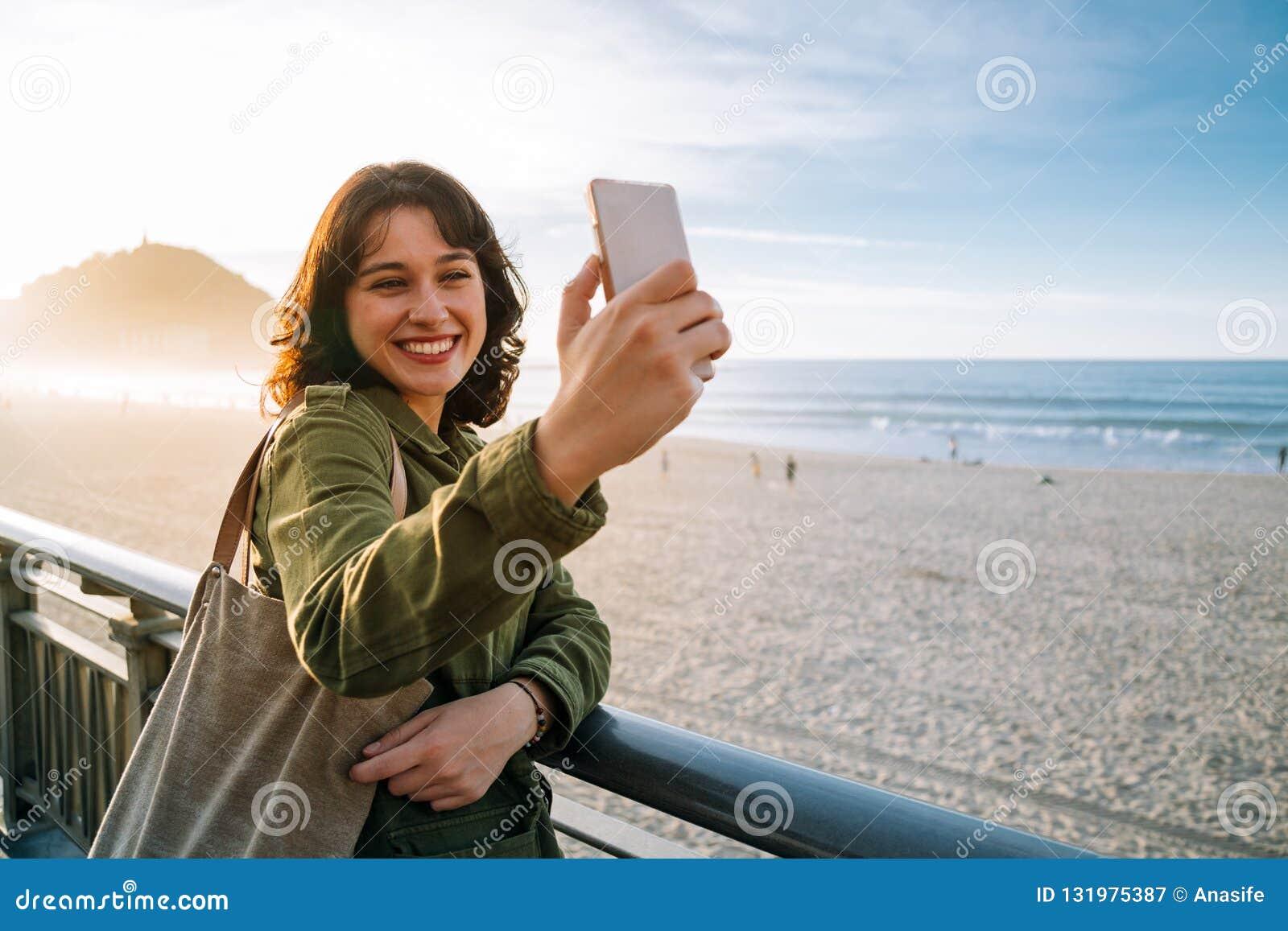 Счастливая туристская женщина принимая selfie с ее умным телефоном