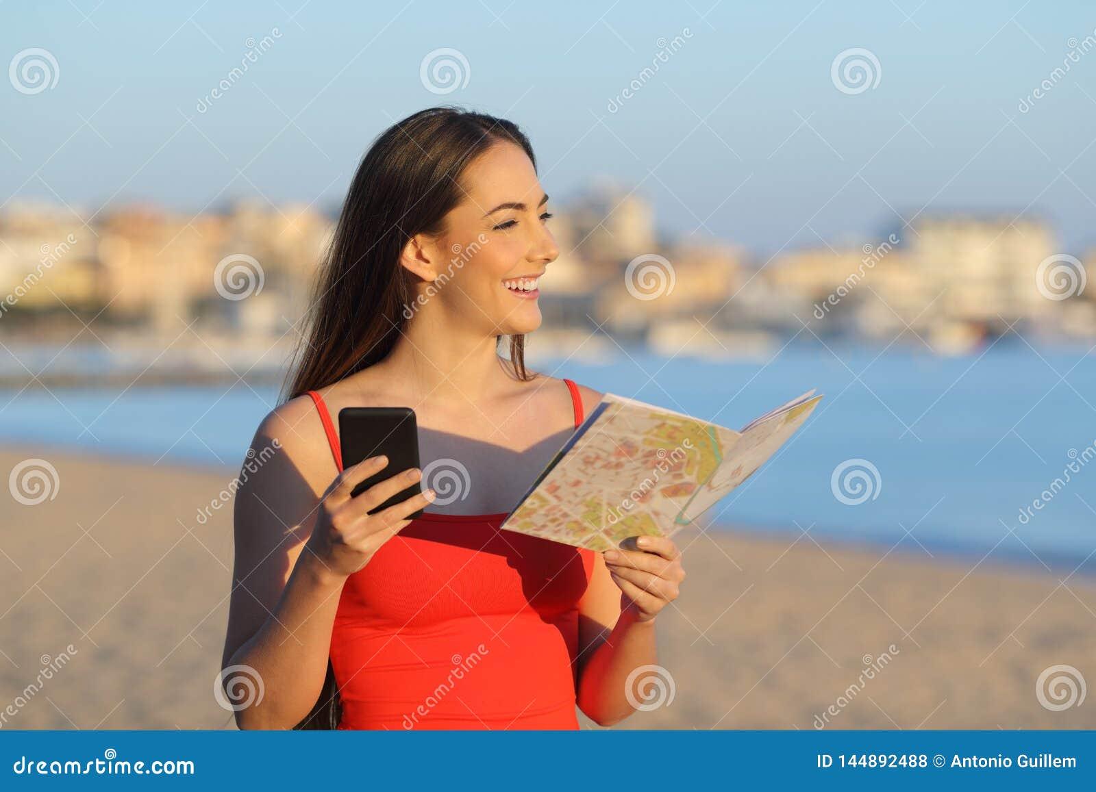 Счастливая туристские держа карта и телефон предусматривая пляж