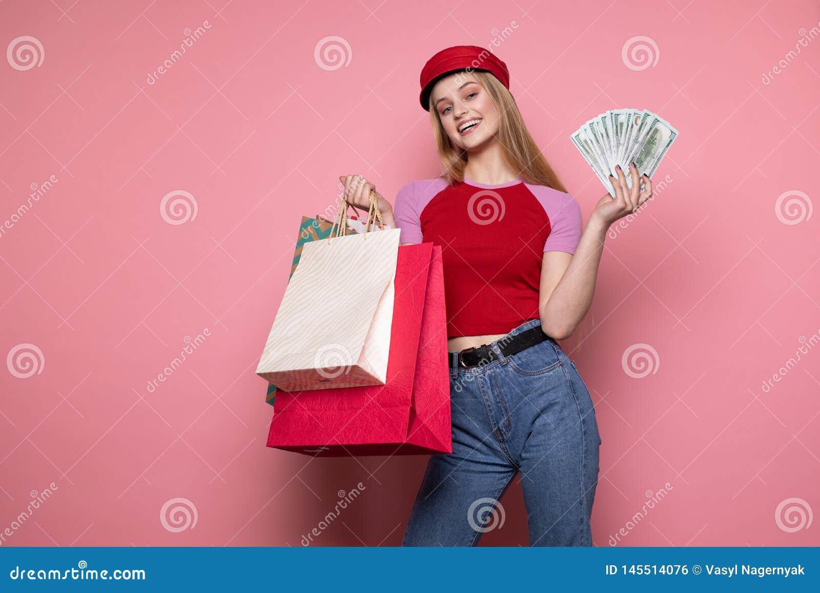 Счастливая усмехаясь девушка в ультрамодной красной шляпе держа красочные хозяйственные сумки