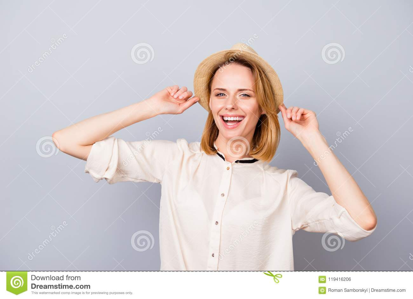 Счастливая усмехаясь женщина в соломенной шляпе имея потеху и положение против