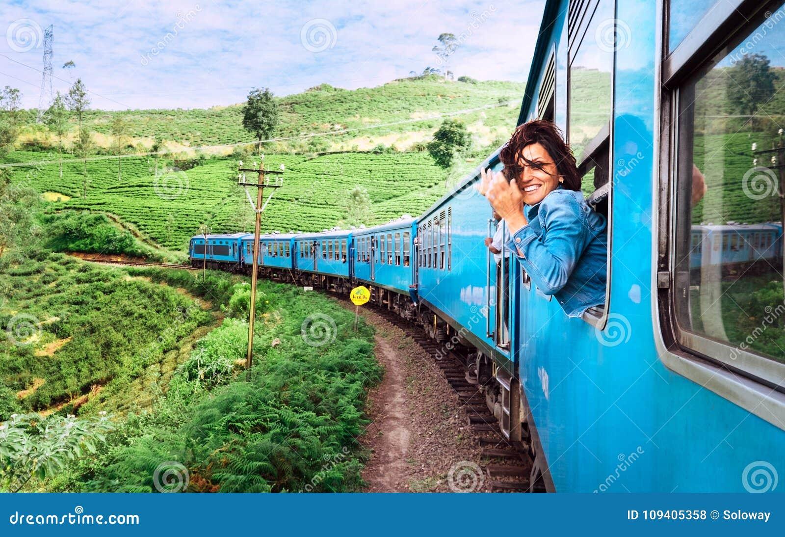 Счастливая усмехаясь женщина смотрит вне от окна путешествуя поездом дальше