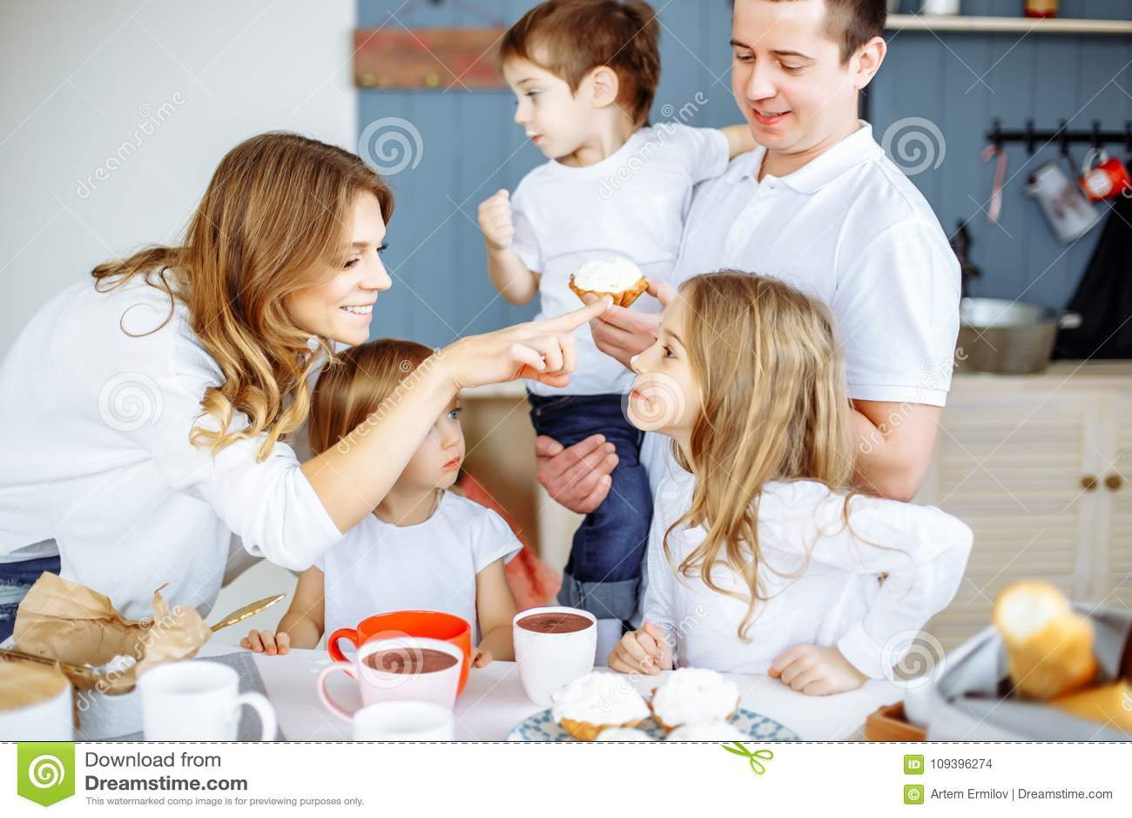 Счастливая усмехаясь кавказская семья имея завтрак в кухне
