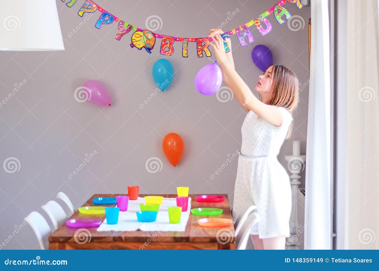 Счастливая preteen девушка настраивая таблицу и вися вверх воздушные шары украшая дом подготавливая к детям день рождения