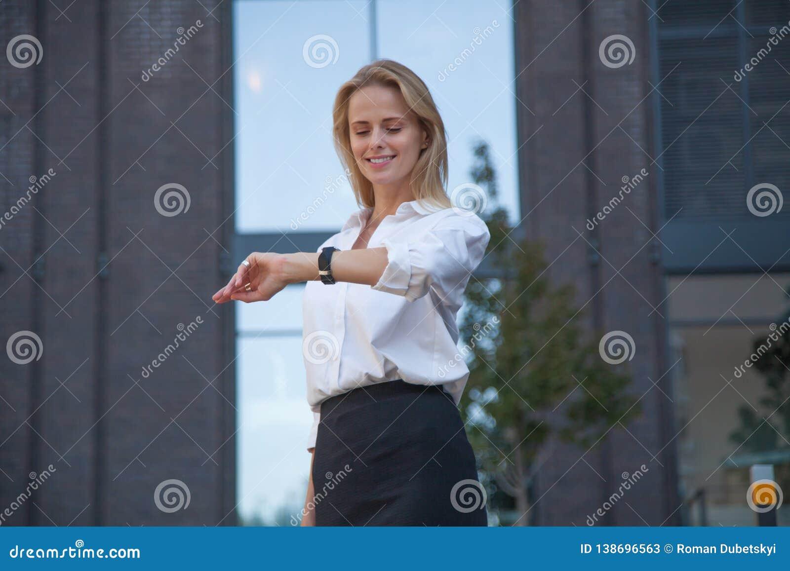 Счастливое белокурое контрольное время бизнес-леди с дозором на ее руке против офисного здания
