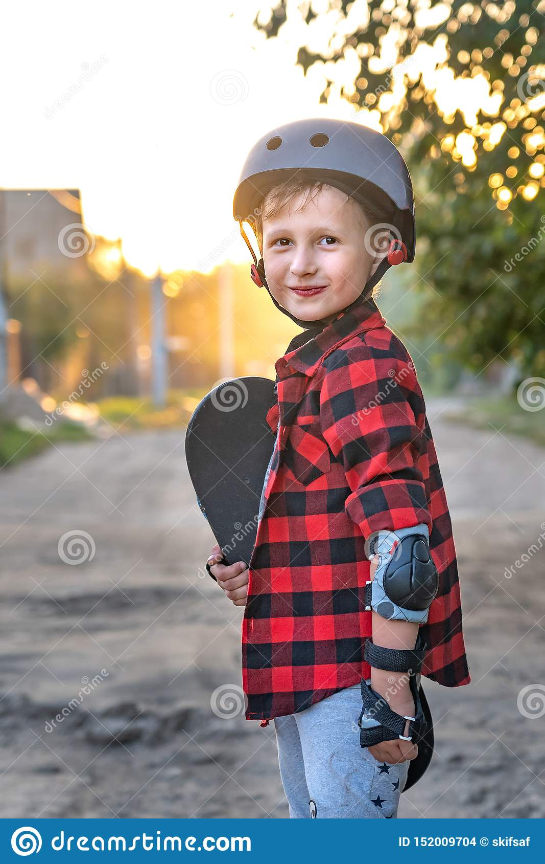 Счастливое положение мальчика на дороге держа конек с его руками ребенок защитил, он положил в наличии перчатки безопасности