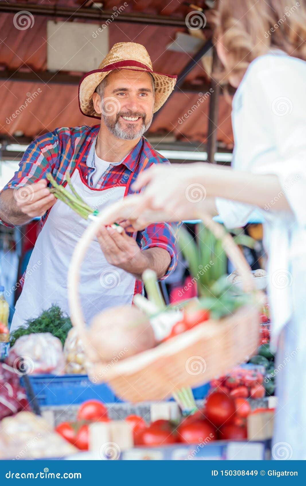 Счастливое старшее положение фермера за стойлом, продавая органические овощи в рынке