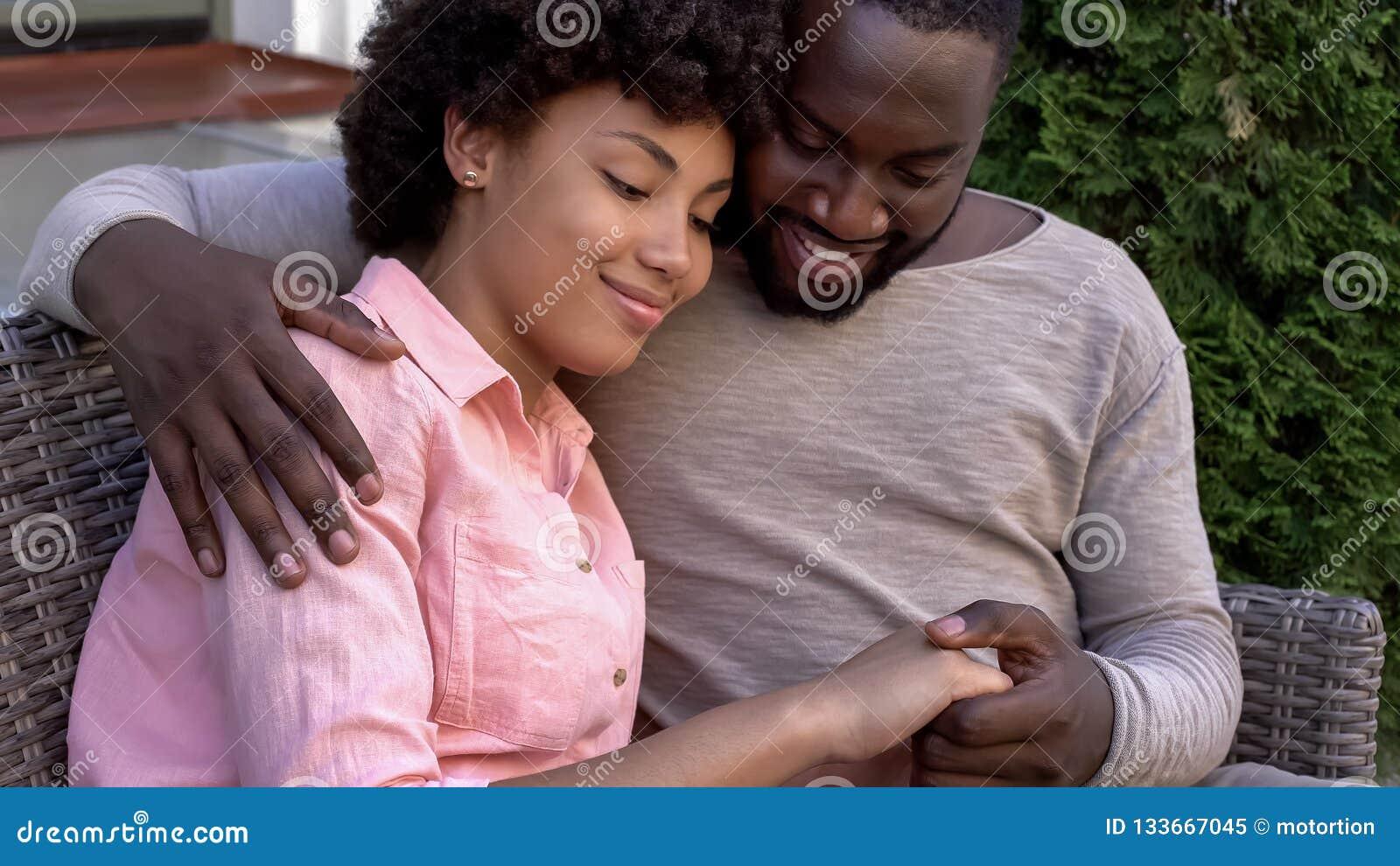Счастливые африканские пары обнимая на стенде, внешней дате в кафе города, сомкнутость