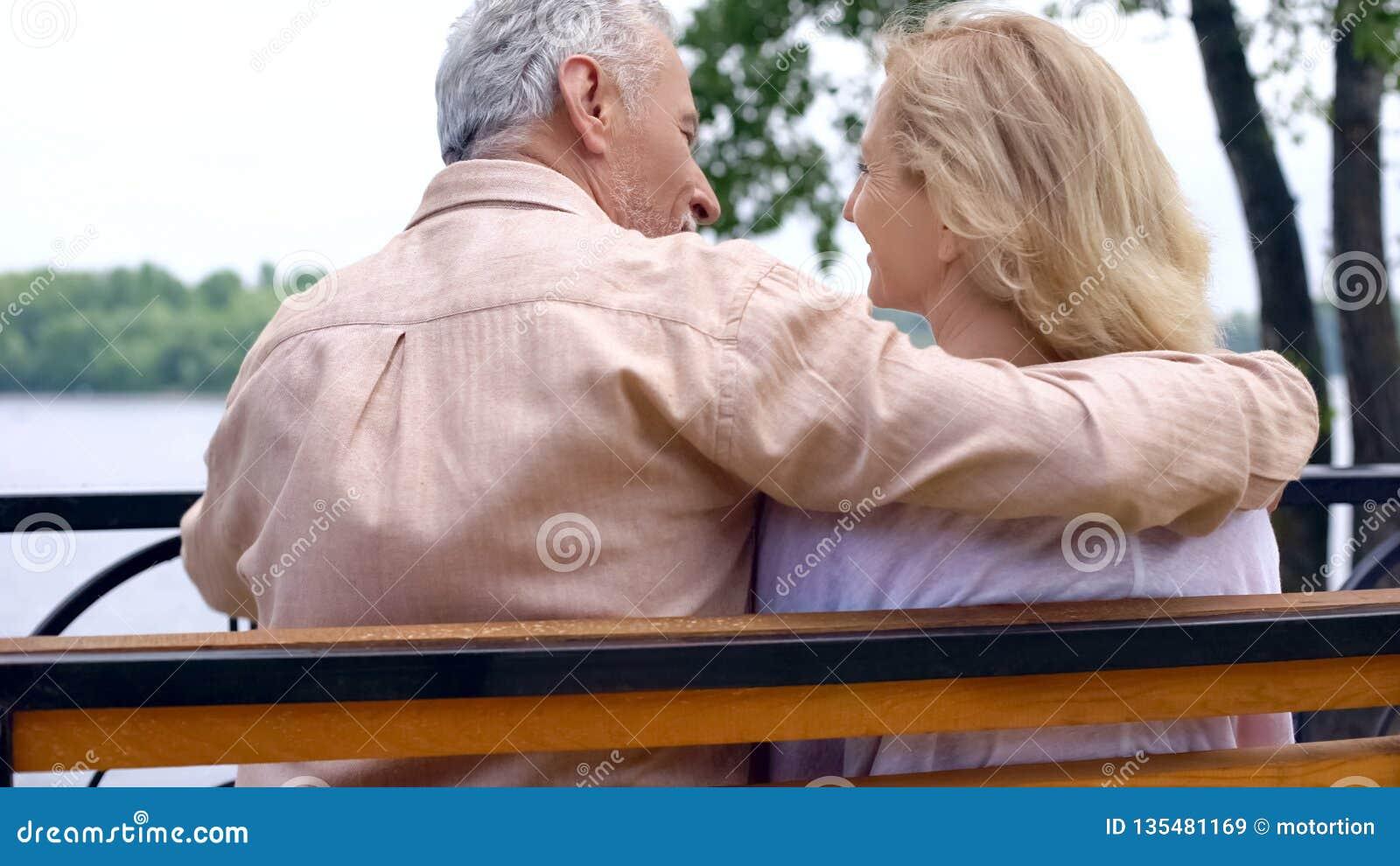 Счастливые выбытые пары ослабляя на скамейке в парке, наслаждаясь выходными снаружи, любовь