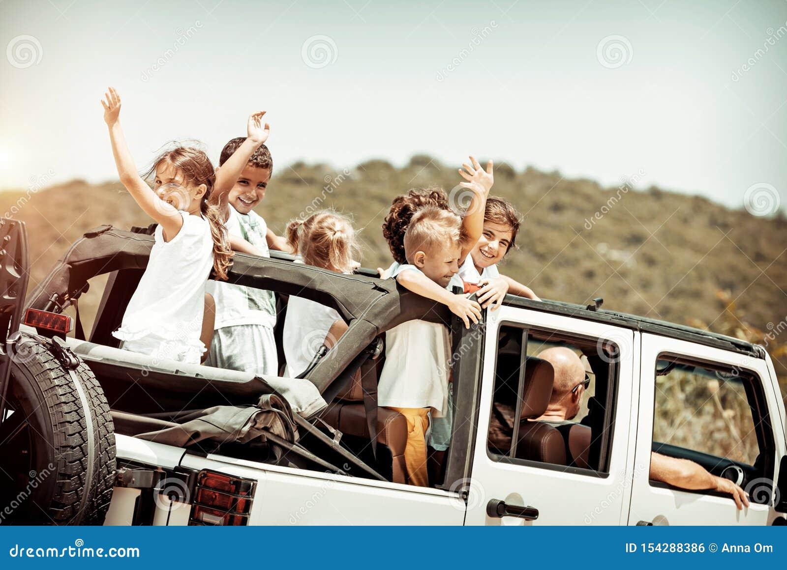 Счастливые дети наслаждаясь поездкой