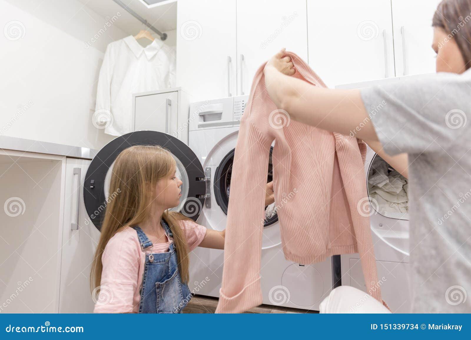 Счастливые домохозяйка матери семьи и дочь ребенка в прачечной со стиральной машиной и одеждами
