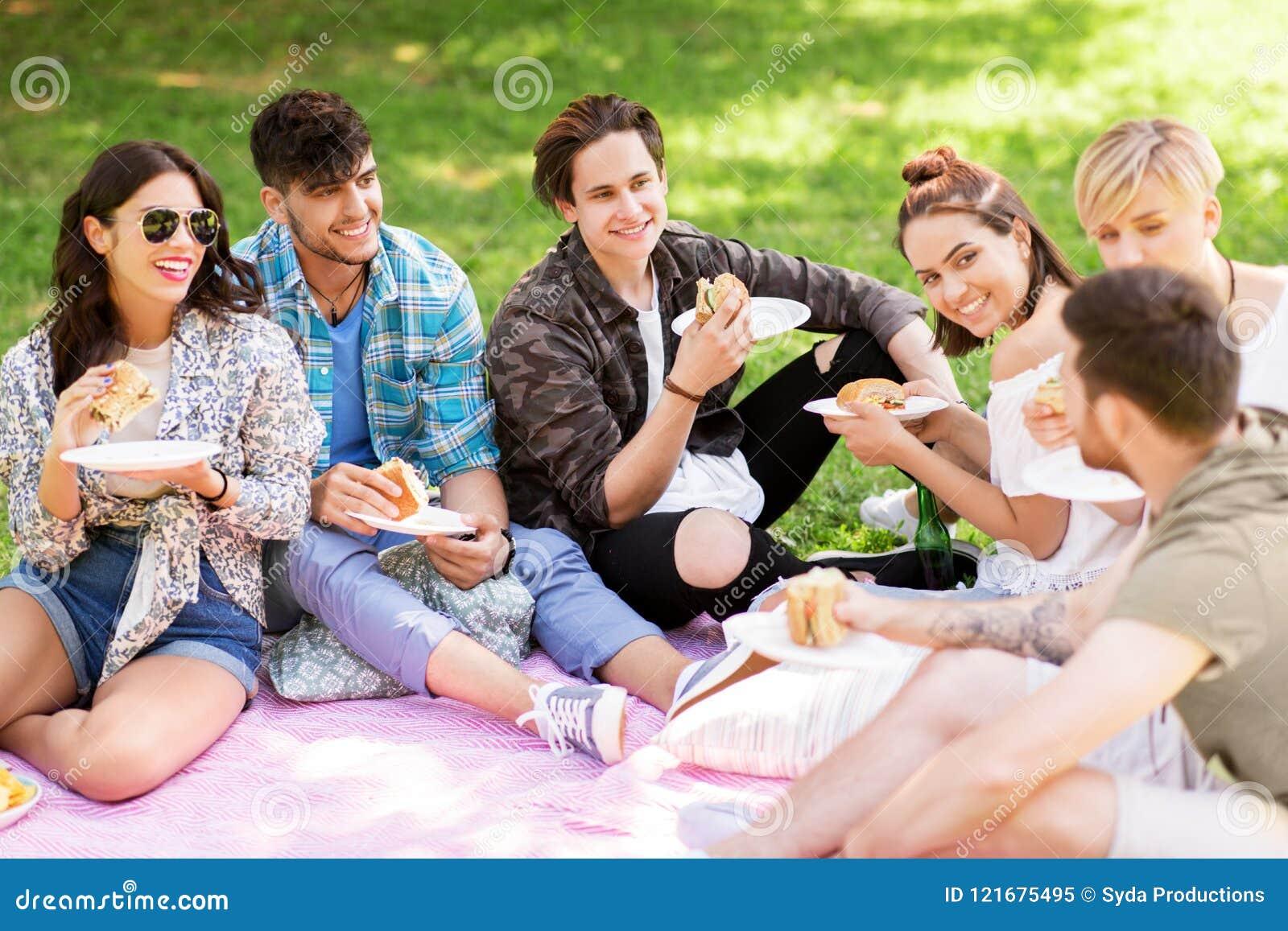Счастливые друзья есть сандвичи на пикнике лета