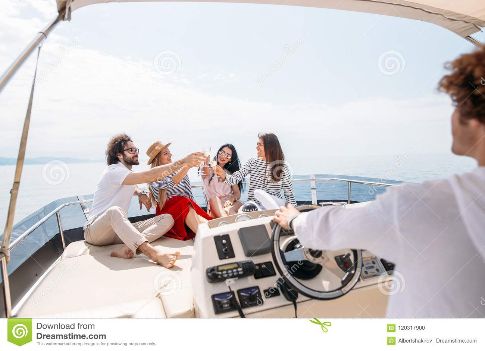 Счастливые друзья clinking стекла шампанского и плавая на яхте