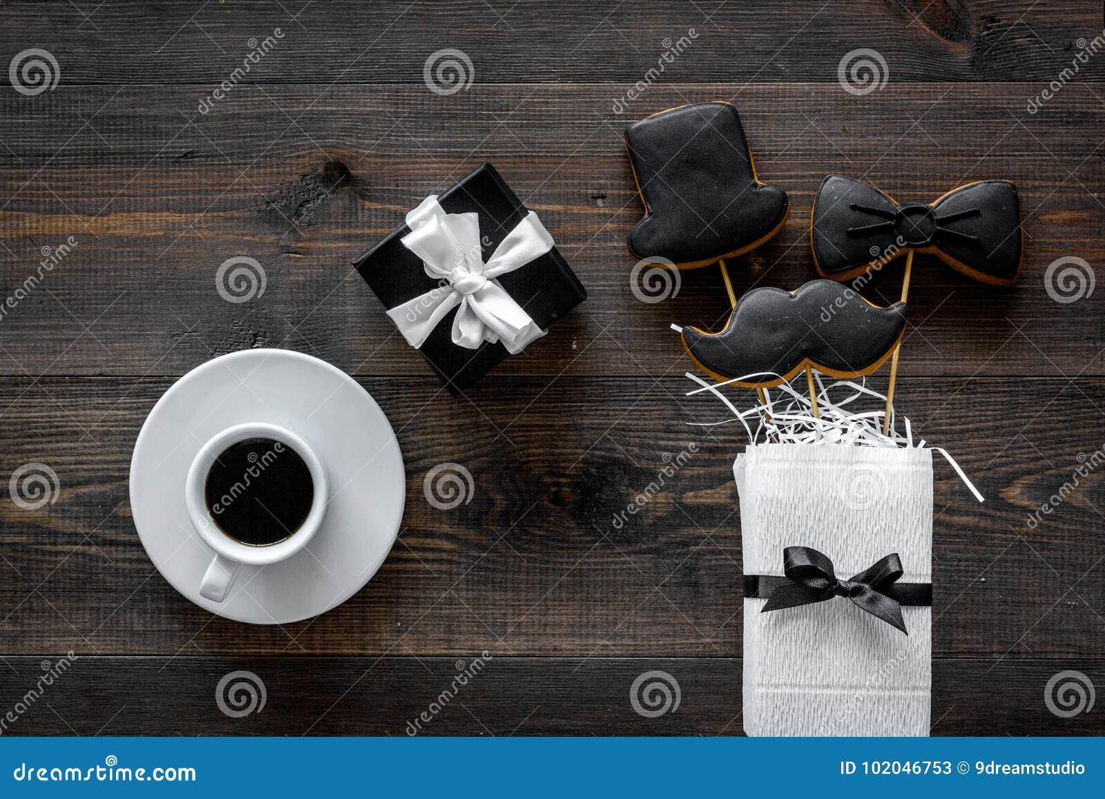 Счастливые карточки дня ` s отца Черный галстук, усик и печенья и подарок шляпы Деревянное взгляд сверху предпосылки стола