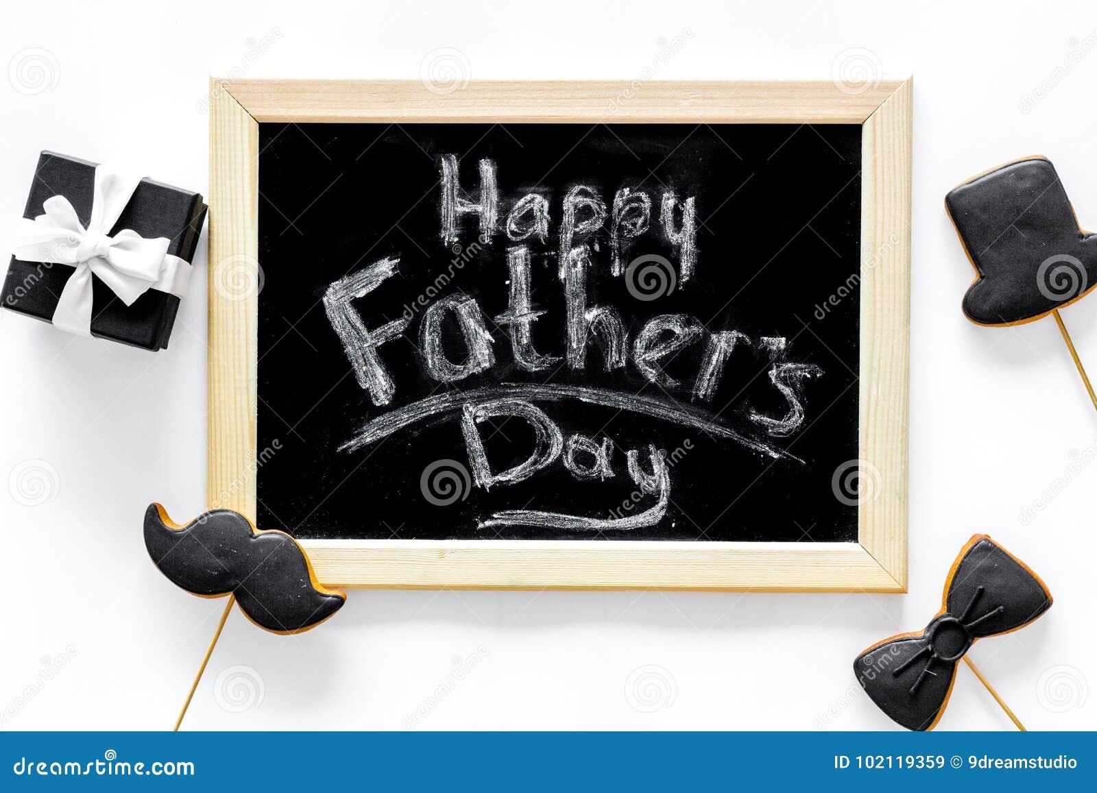 Счастливые карточки дня ` s отца Черный галстук, усик и печенья и подарок шляпы Белое взгляд сверху предпосылки стола