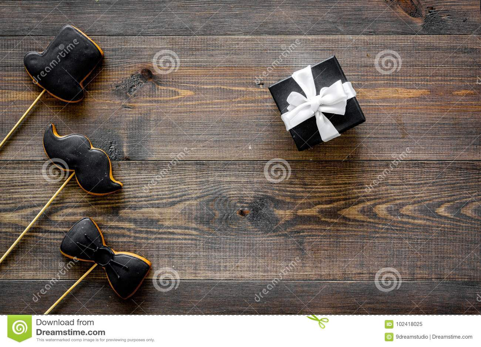 Счастливые карточки дня ` s отца Черный галстук, усик и печенья и подарок шляпы деревянный модель-макет взгляд сверху предпосылки