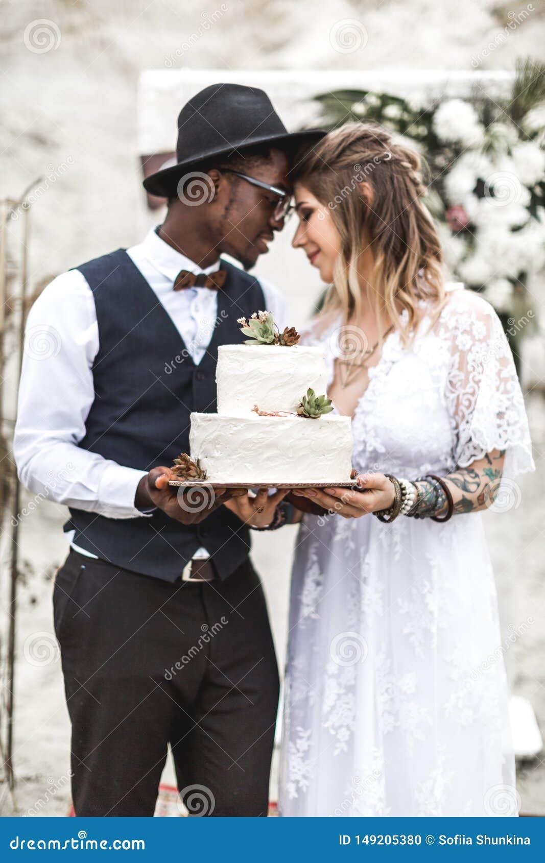 Счастливые красивые пары имеют потеху с украшенным свадебным пирогом с succulents в загородном стиле Свадьба Boho