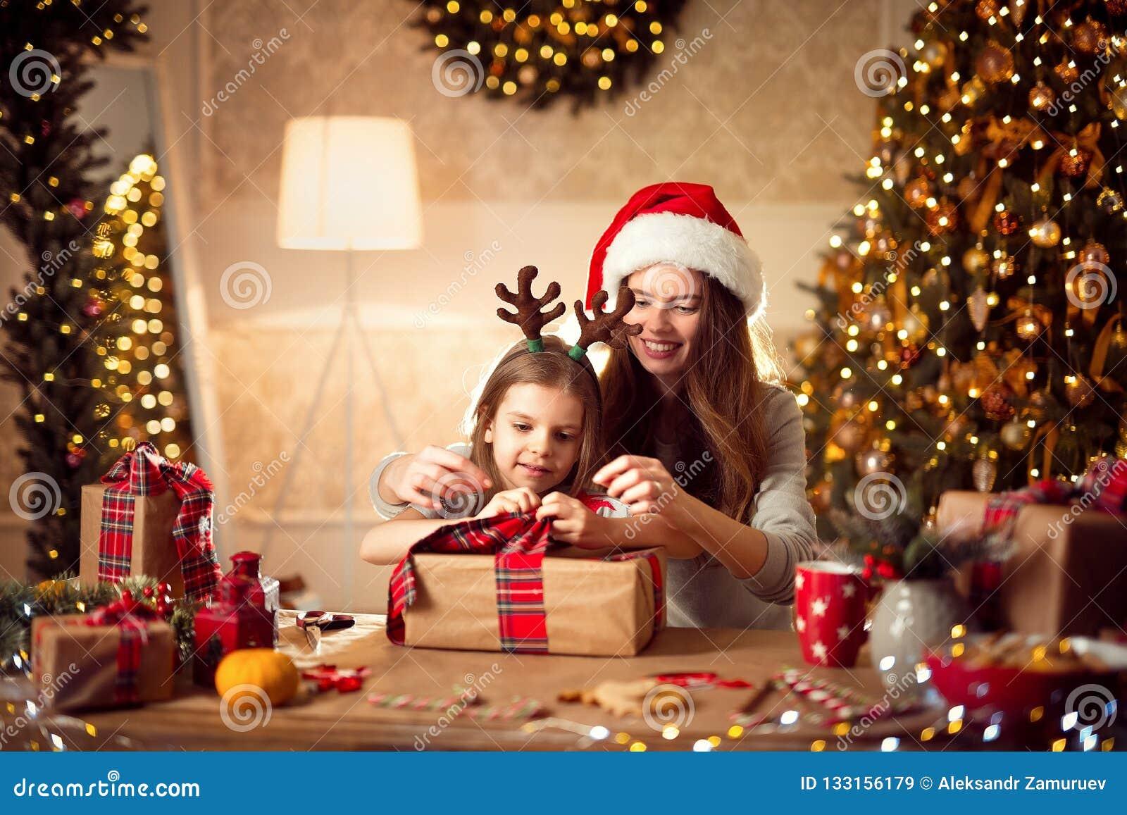 Счастливые мать и ребенок семьи пакуют подарки рождества