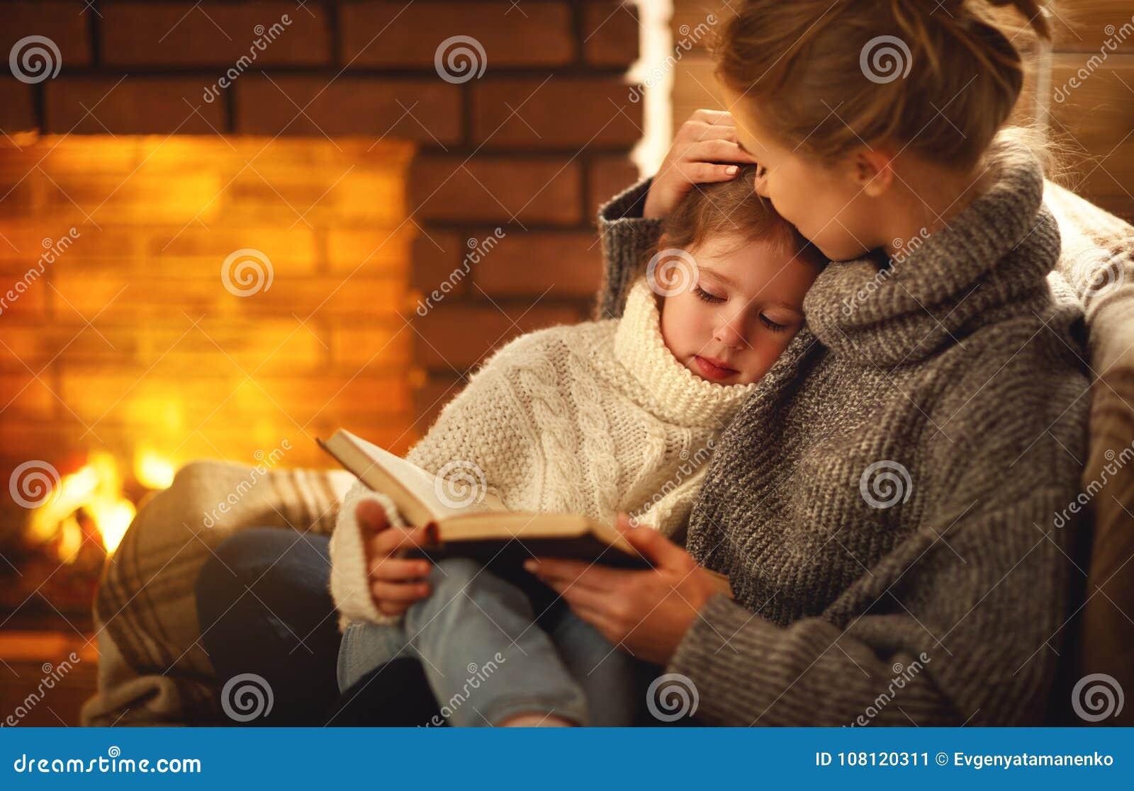 Счастливые мать семьи и дочь ребенка прочитали книгу на eveni зимы