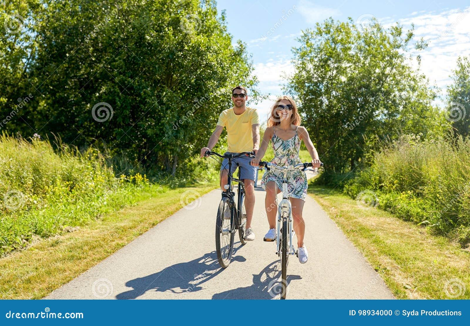 Счастливые молодые велосипеды катания пар в лете
