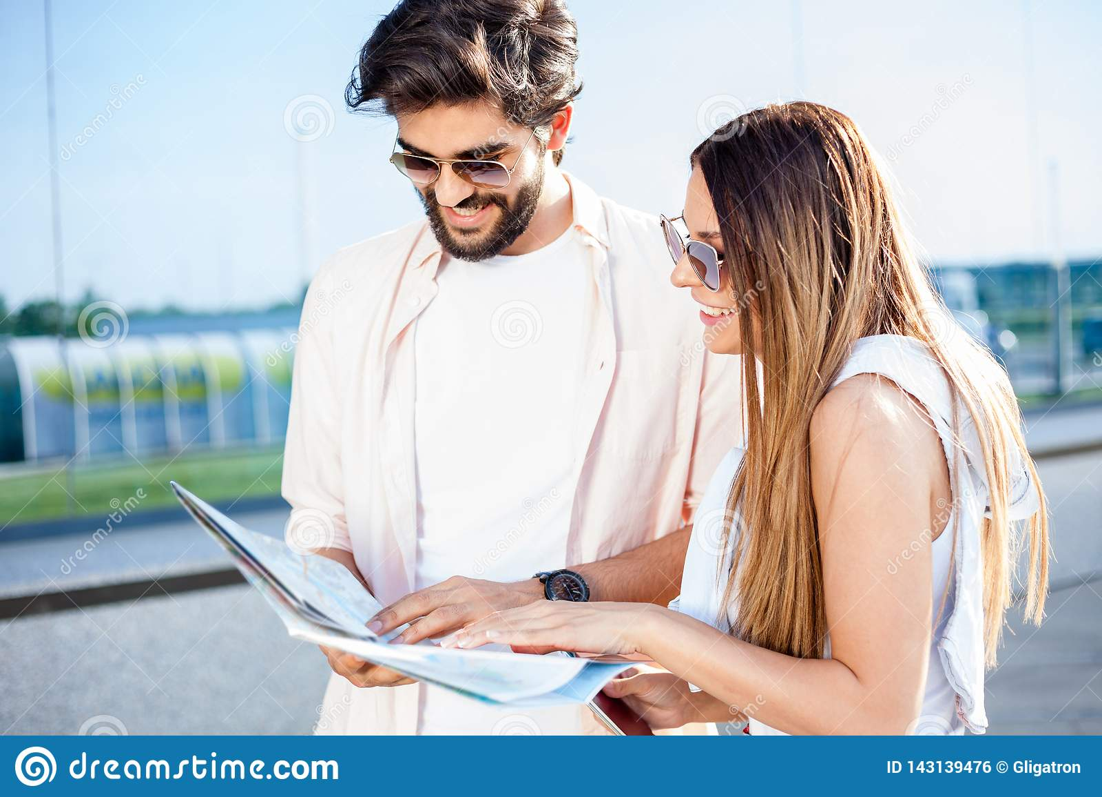 Счастливые молодые пары смотря карту и ища направлений