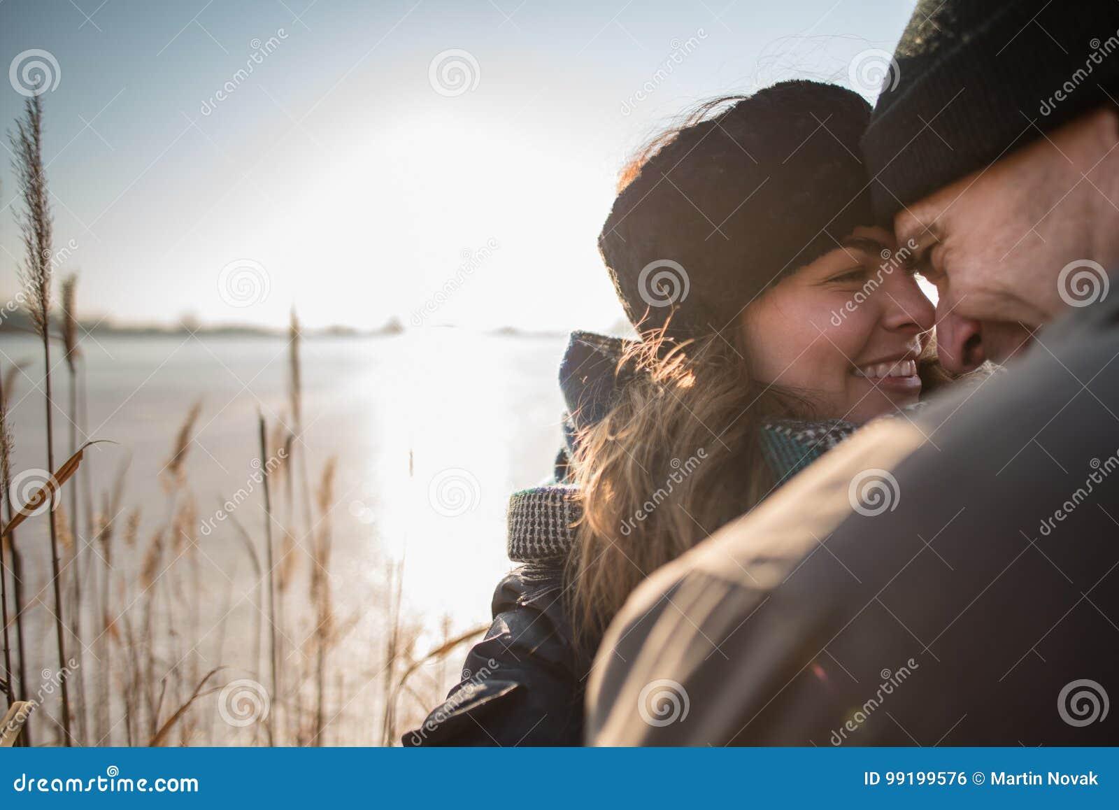 Счастливые пары обнимая, солнце в предпосылке