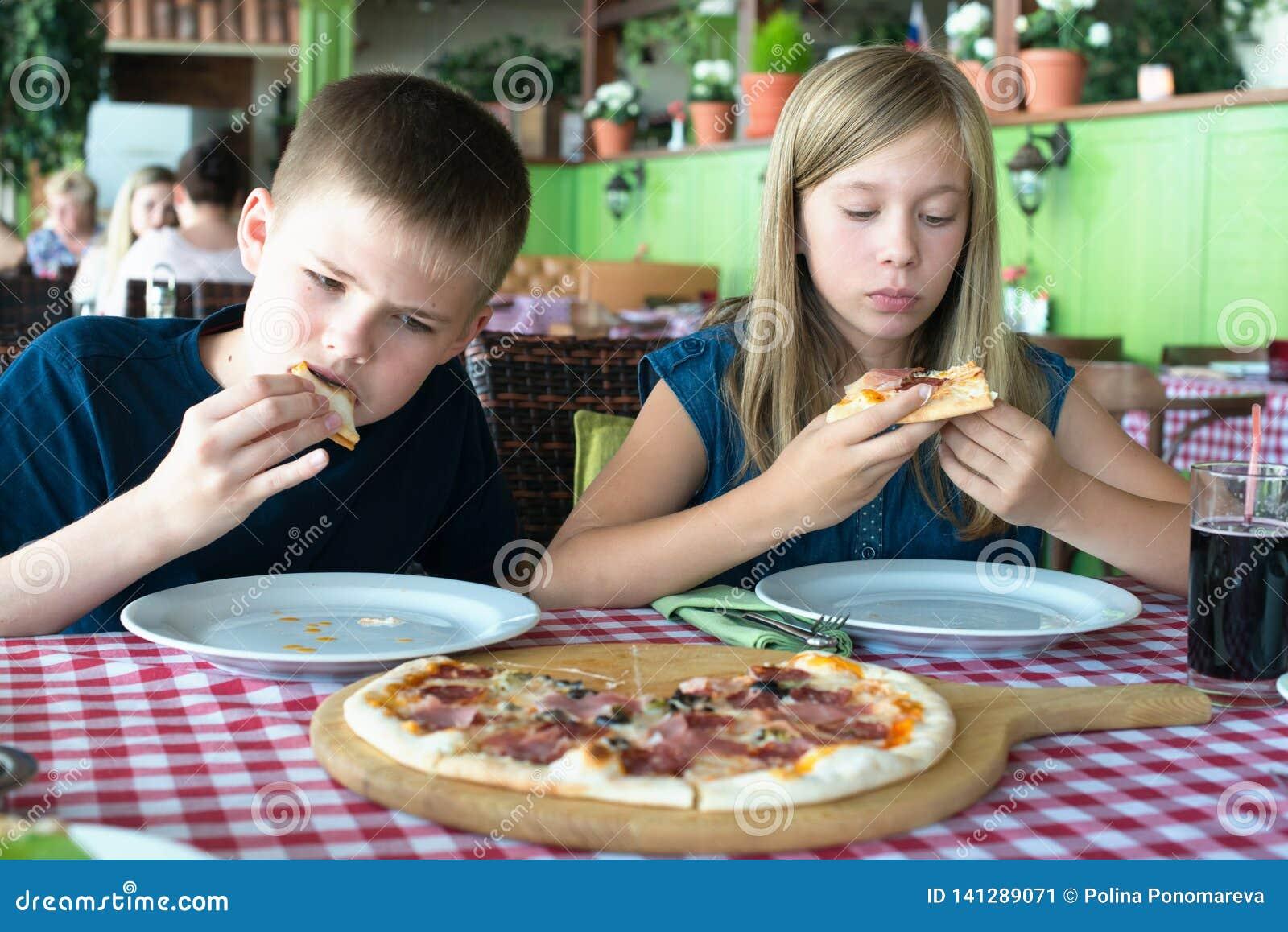 Счастливые подростки есть пиццу в кафе Друзья или братья имея потеху в ресторане